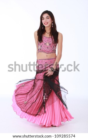 Young pretty brunette Muslim woman wearing traditional Indian cultural dress in pink satin and beaded embroidery and elaborate earrings with jewels and beads. - stock photo