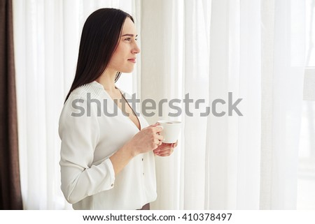 Young pretty brunette stands and looks aside and drinking coffee indoor