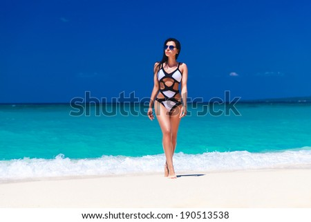 young pretty brunette with long hair in black and white swimsuit walks on tropical beach - stock photo