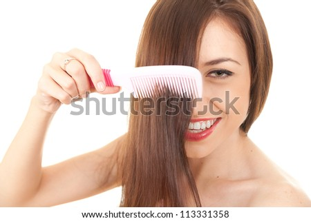 young pretty brunette woman combing her beautiful long hair, white background - stock photo