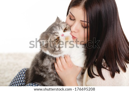 Young pretty brunette woman holding her lovely exotic cat with isolated on a white background