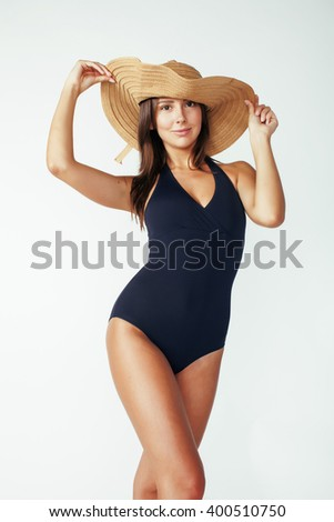 young pretty brunette woman wearing summer hat and swimsuit isolated on white background preparing to vacations - stock photo