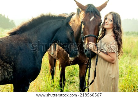 Young pretty brunette woman with horses in summer field