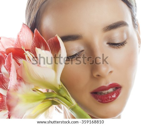 young pretty brunette woman with red flower amaryllis close up isolated on white background. Fancy fashion makeup, bright lipstick, modern