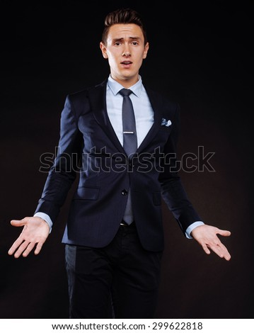 young pretty business man standing on black background, modern hairstyle