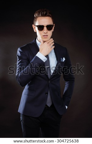 young pretty business man standing on black background, modern hairstyle, talking on phone