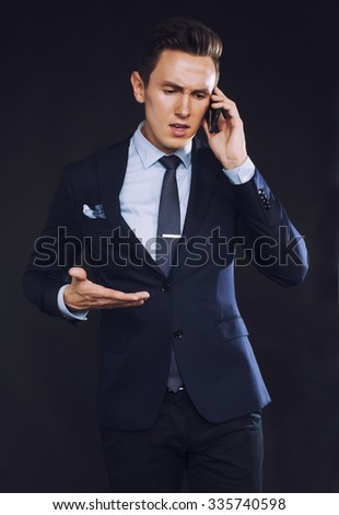 young pretty business man standing on black background, modern hairstyle, talking on phone emotional