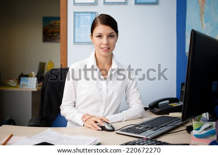 Young pretty business woman at workplace in office - stock photo