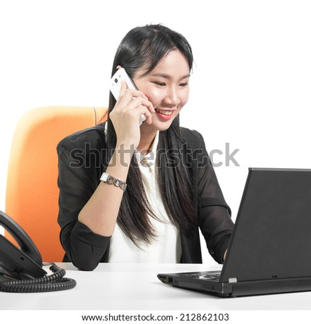 Young pretty business woman using cell phone looking at laptop computer with phone on desk