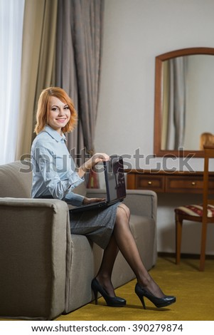 Young pretty business woman with laptop sitting on couch in the hotel room