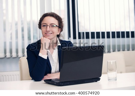 Young pretty business woman with notebook in the office. smile on a camera