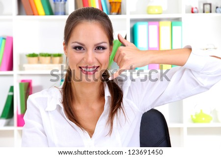 Young pretty business woman with phone working at office. Contact us - stock photo