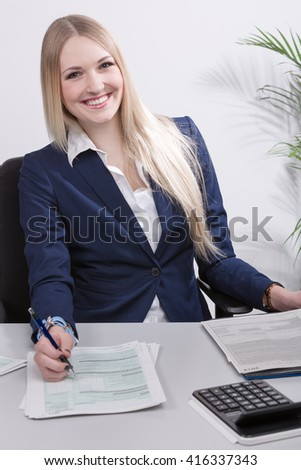 young pretty business woman works at desk with fun