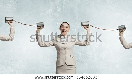 Young pretty businesswoman attaching tin phone to ear