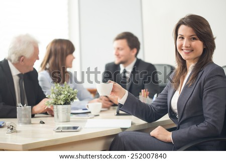 Young pretty businesswoman during company assemblage - stock photo