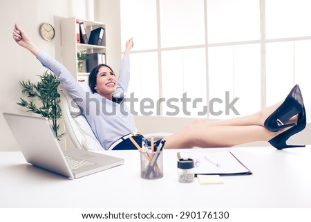 Young pretty businesswoman in the office sitting in office chair, hands up and with her feet up on a desk. In the background you can see the shelves with binders.