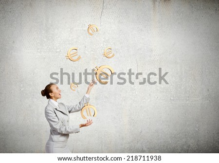 Young pretty businesswoman juggling with euro symbols - stock photo