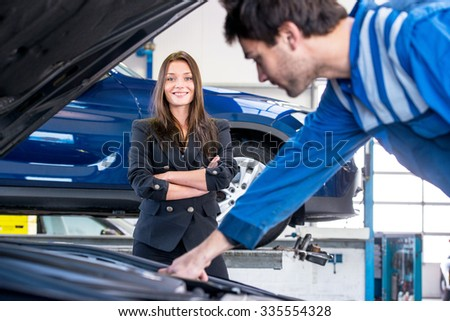Young, pretty businesswoman looks happily at  the mechanic, whilst heâ??s fixing her car in a garage, aimed at customer service and instant assistance - stock photo