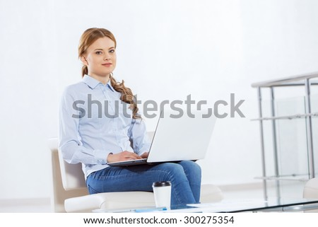 Young pretty businesswoman sitting and using laptop