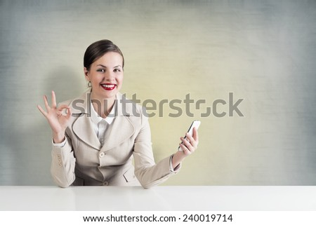 Young pretty businesswoman sitting at table with mobile phone in hand - stock photo