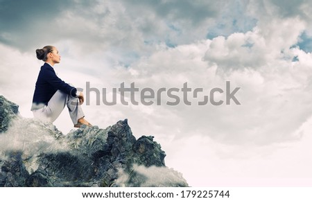 Young pretty businesswoman sitting on top of mountain
