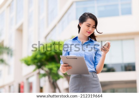 Young pretty businesswoman texting outdoors - stock photo