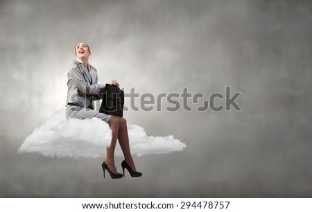 Young pretty businesswoman with briefcase in hands sitting on cloud