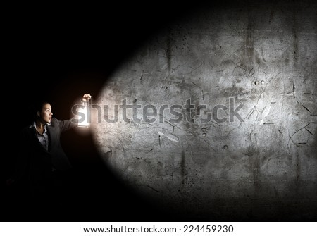 Young pretty businesswoman with lantern in darkness - stock photo