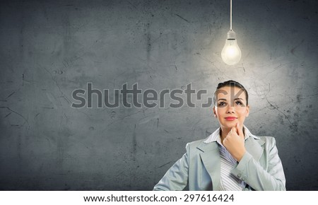 Young pretty businesswoman with light bulb over head - stock photo