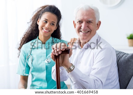 Young pretty caring happy nurse taking care of older smiling man with walking stick