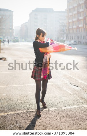 young pretty caucasian brown hair woman, seen from behind, posing in the street of the city, playing and dancing with her colorful scarf - carefree, youth, happiness concept - stock photo