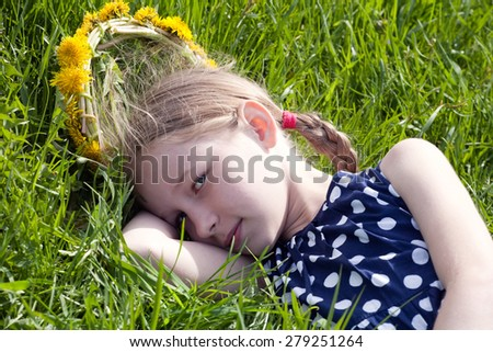 young pretty caucasian girl in yellow dandelions garland lying on green grass, face closeup - stock photo