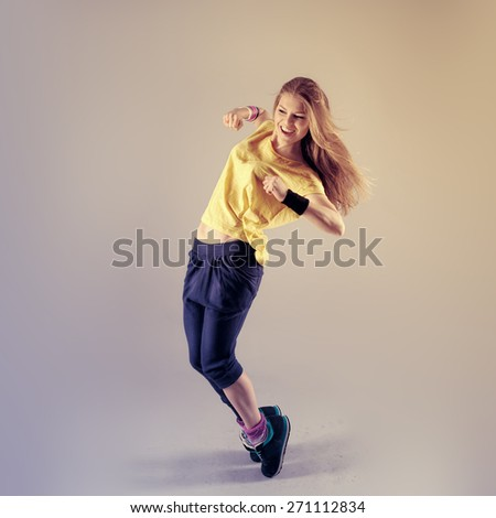 Young pretty Caucasian hip hop girl dancing with fun. Active fitness trainer posing in studio.  - stock photo
