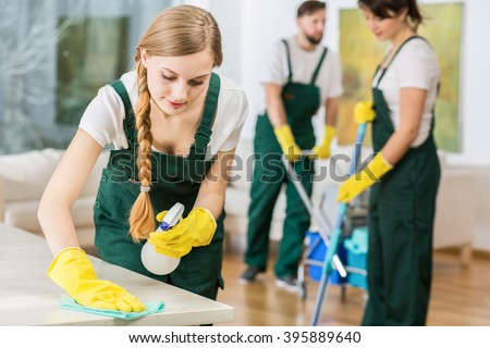 Young pretty cleaning girl in uniform polishing the marble table - stock photo