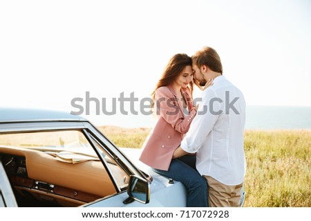 Young Pretty couple embracing while leaning on a vintage car outdoors
