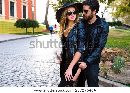 Young pretty couple in love hugs on the street of old town, wearing stylish total black leather rock n roll clothes and sunglasses. Outdoor fashion portrait of lovers. - stock photo