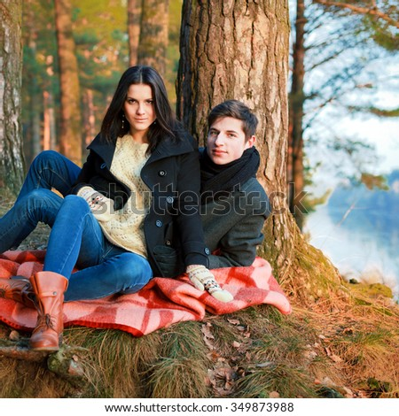 Young pretty couple in love posing outdoor in winter forest  - stock photo