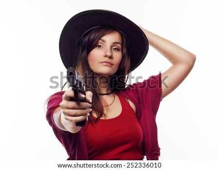 Young pretty cowgirl holding gun - stock photo