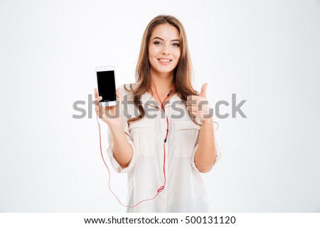 Young pretty cute girl with earphones listening music with smartphone and showing thumbs up gesture isolated on a white background