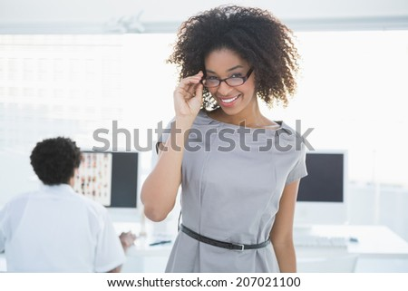 Young pretty editor smiling at camera with colleague working behind her in creative office - stock photo