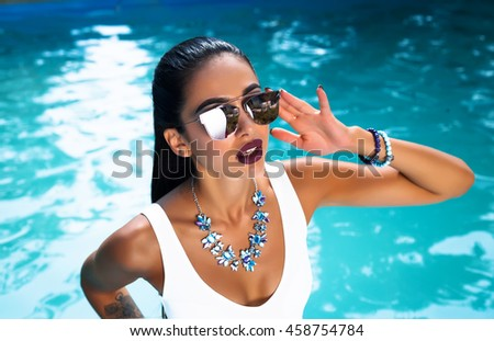 Young pretty fashion sport woman posing outdoor in summer on tropic island in hot weather in bikini on pool party.fashion photo of beautiful tanned woman in elegant black bikini relaxing beside  pool  - stock photo