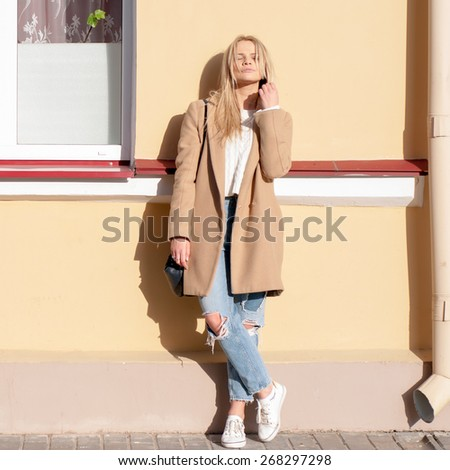 Young pretty fashionable blonde woman dressed in ripped jeans and beige coat basking in the sun   - stock photo