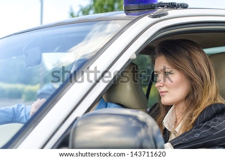 Young pretty female agent driving the car - stock photo