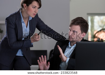Young pretty female boss threatening to her young handsome employee - stock photo