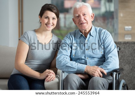 Young pretty female caretaker and elderly man on a wheelchair - stock photo