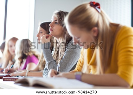 young pretty female college student sitting in a classroom full of students during class - stock photo