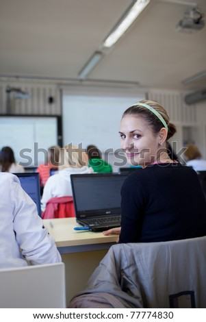 young, pretty female college student sitting in a classroom full of students during class (shallow DOF) - stock photo