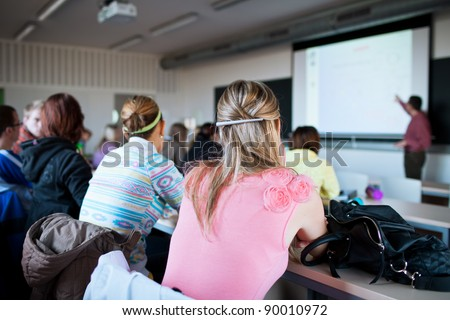 young, pretty female college student sitting in a classroom full of students during class (shallow DOF; color toned image) - stock photo