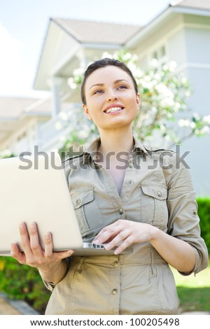 Young pretty female realty agent with laptop presenting beautiful detached house - stock photo