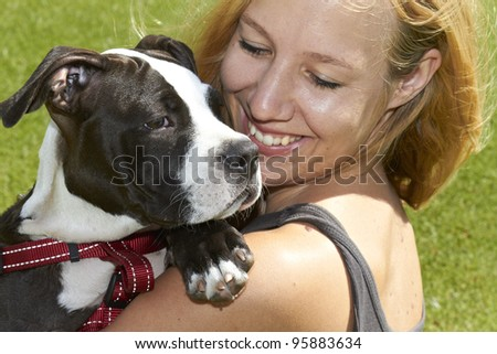 Young pretty female smiling at Pit Bull puppy